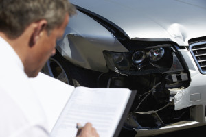 Illustration of an insurance claims adjuster examining a vehicle. (monkeybusinessimages/iStock/Thinkstock)