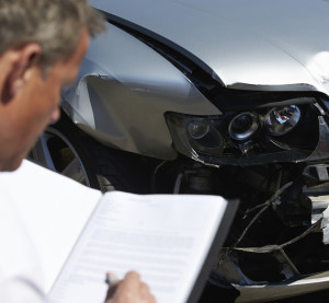 Illustration of an insurance claims adjuster examining a vehicle. (monkeybusinessimages/iStock/Thinkstock)
