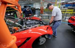 An employee at General Motors' Bowling Green, Ky., Corvette plant installs a front fender bracket on a 2014 Corvette Stingray on June 27, 2013. (AJ Mast for Chevrolet/© General Motors file)