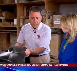 Mike Orso, owner of Nick Orso's Body Shop, shows an aftermarket part to Rachel Polansky, reporter for the Syracuse, N.Y., WSYR station in this screenshot from WSYR video. (Screenshot from www.localsyr.com video)