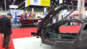 Future materials: Bodies-in-white of a carbon-fiber BMW i8, foreground, and ultra-high-strength steel Chrysler 200, background, are displayed at NACE|CARS in Detroit in July 2015. (John Huetter/Repairer Driven News)