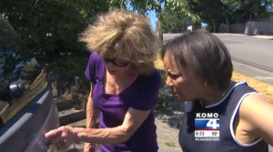 """Seattle KOMO reporter Connie Thompson, right, seen in a screenshot from a video posted July 1, 2015, has described how an attempt to save $215 through parking lot dent repair left Sandi Finley, left, with """"a mess on her car and a dent on her wallet."""" (Screenshot from www.komonews.com)"""