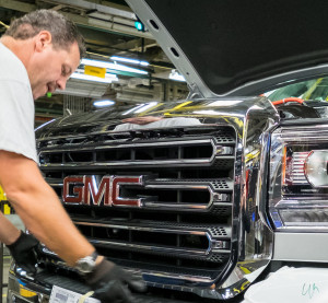 General Motors employee Al Havens attaches a grille to a GMC Sierra 2500 HD on Aug. 4, 2015, in Flint, Mich. (Steve Fecht for General Motors/Copyright General Motors)