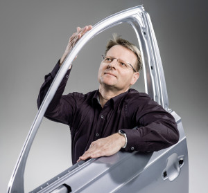 Audi Q7 door developer Wolfgang Faaß is shown with one of the aluminum Q7 doors. (Provided by Audi)