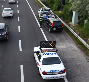 A Toronto, Ontario, police car helps direct traffic on Don Valley Parkway on June 26, 2013, while a car is being towed by a Canadian Automobile Association truck.  (bukharova/iStock Editorial/Thinkstock file)