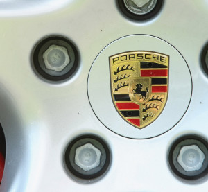 The logo and hood ornament of German automaker Porsche is seen on the wheel of a Porsche car at a dealership on July 21, 2009, in Berlin, Germany. (Sean Gallup/Getty Images News/Thinkstock file)