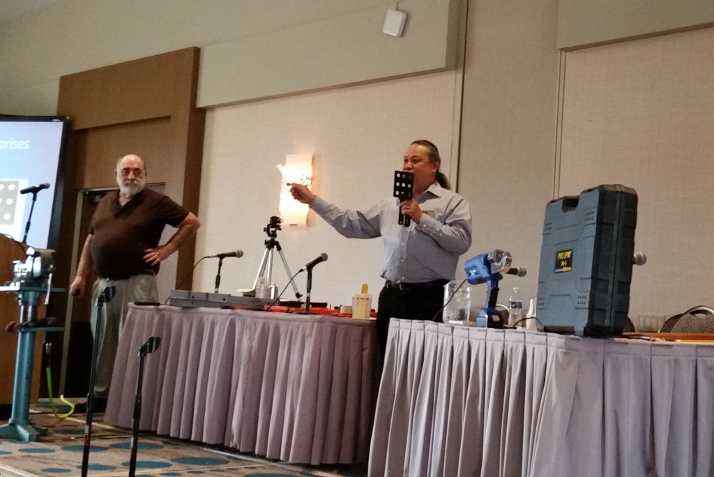 Kye Yeung of the Society of Collision Repair Specialists Education Committee, right, demonstrates a GL Enterprises Shiner at the January 2016 Collision Industry Conference while Toby Chess of the committee looks on. (John Huetter/Repairer Driven News)