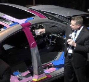 A Honda Canada representative discusses the 2016 Civic next to a color-coded body-in-white cutaway in this screenshot from Canadian Collision Industry Forum video. (Screenshot from CCIF video)