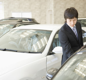 A car dealer opens a door in what appears to be a tight fit. (DAJ/amana images/Thinkstock)