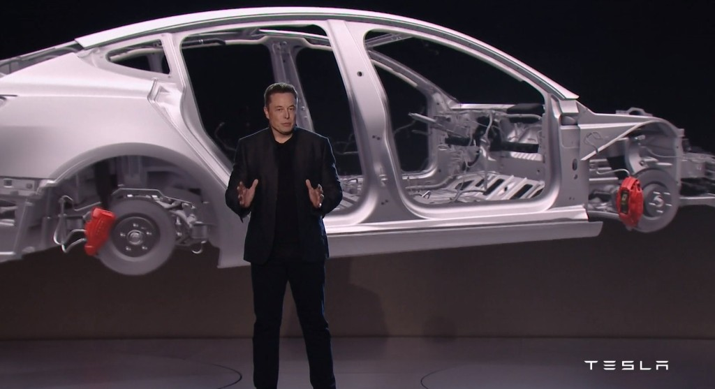 This screenshot from Tesla videos shows a rendering of the Tesla Model 3 body-in-white behind CEO Elon Musk. (Screenshot from Tesla video)