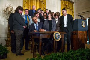 Democratic President Barack Obama on March 13, 2014, signs a memorandum directing Labor Secretary Tom Perez to overhaul national overtime for salaried workers. (Lawrence Jackson/Official White House Photo)