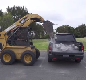 In this screenshot from Honda video, more than 800 pounds of landscaping blocks are dumped on a 2017 Honda Ridgeline. (Screenshot from Honda video at www.YouTube.com)
