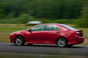 An unspecified model year of the 2012-14 Toyota Camry drives in this promotional image. (Provided by Toyota)