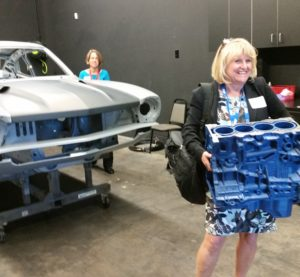 Debbie Teter of Garmat holds a 3-D-printed engine block during the SCRS SEMA Garage tour. (John Huetter/Repairer Driven News)
