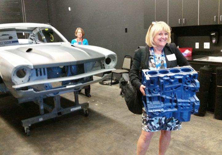 Debbie Teter of Garmat holds a 3-D-printed engine block during the SCRS SEMA Garage tour. (John Huetter/Repairer Driven News)