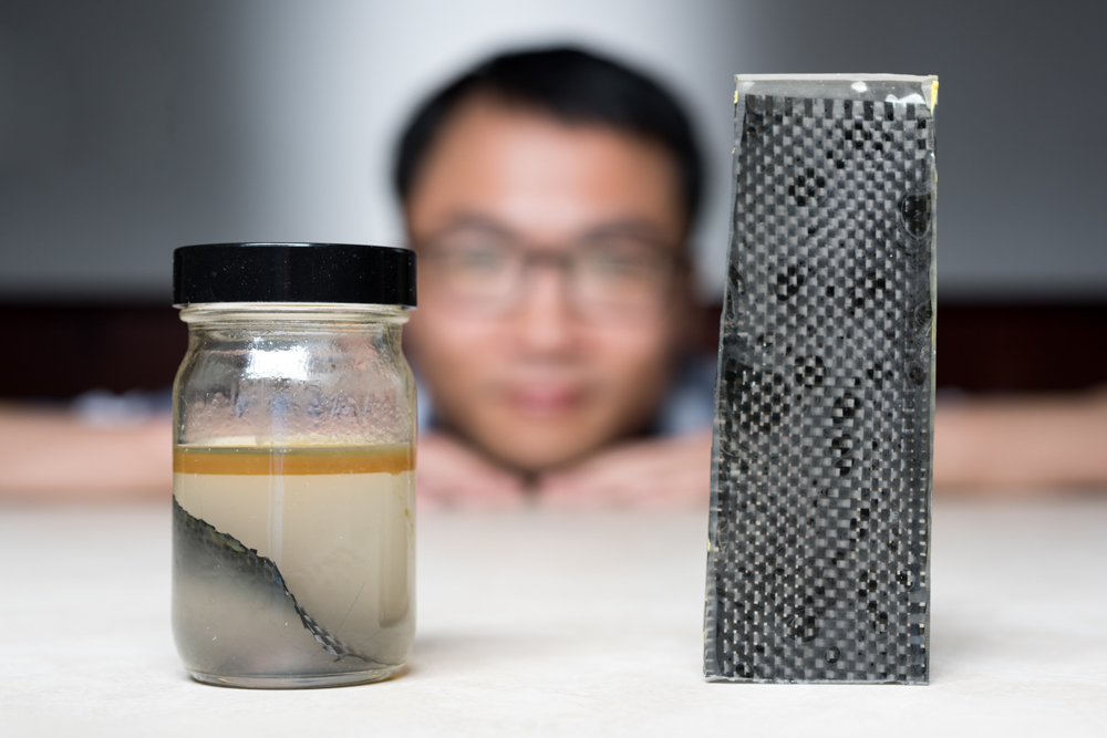 Kai Yu, a former postdoctoral researcher in The George W. Woodruff School of Mechanical Engineering at Georgia Tec, sits behind a piece of carbon fiber composite immersed in alcohol. (Rob Felt/Georgia Tech)