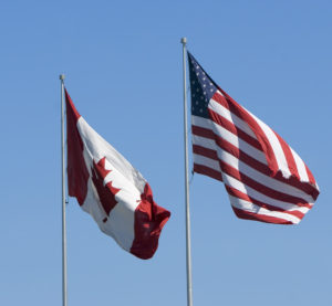Canadian and U.S. flags. (supertramp/iStock)