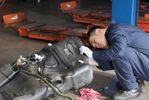 A mechanic works on a gas tank. (Eliza Snow/iStock)